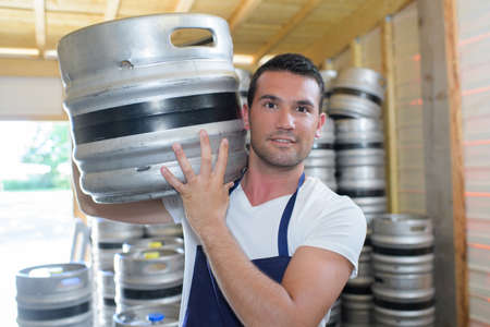 Photo pour worker carrying barrel with beer at the brewery - image libre de droit