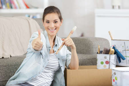 Photo pour woman painting a cabinet with brush thumbs up - image libre de droit