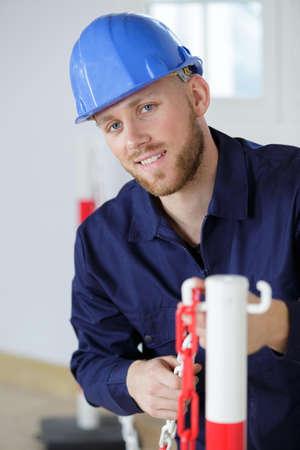 Photo pour builder putting up a safety chain around work area - image libre de droit