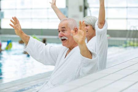 Photo pour senior couple waving in a swimming pool - image libre de droit