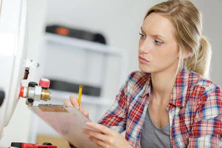Photo pour a female plumber writing notes - image libre de droit