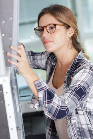 Photo pour beautiful female clerk searching for proper document - image libre de droit