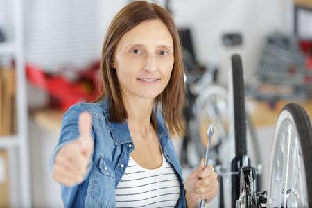 Photo pour young woman with bike showing thumb up - image libre de droit