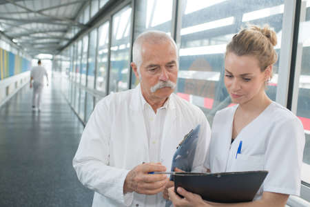 Photo pour doctor and nurse discussing over a medical report in hospital - image libre de droit