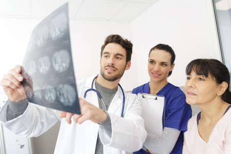 Photo pour doctor nurse and female patient in office looking an xray - image libre de droit