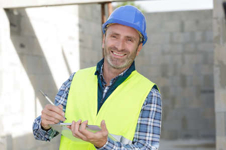 Photo pour confident engineer holding blueprint outdoors in construction site - image libre de droit