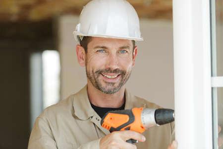 Photo pour smiling man is fixing a window - image libre de droit