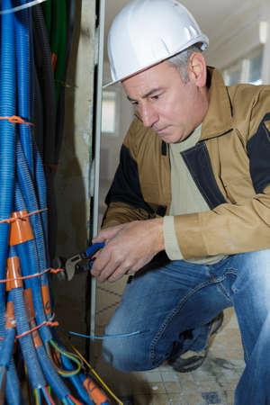 Photo pour senior worker twisting tie around bundle of cable trunking - image libre de droit