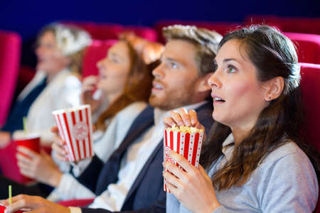 Photo pour scared friends watching film with popcorn in the cinema - image libre de droit