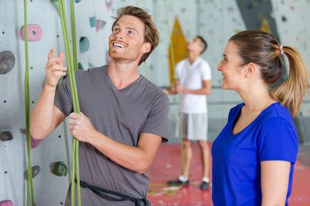 Photo pour climber checking ropes before climbing indoor wall - image libre de droit