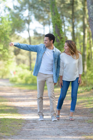 Photo pour young cheerful couple walking in the park - image libre de droit