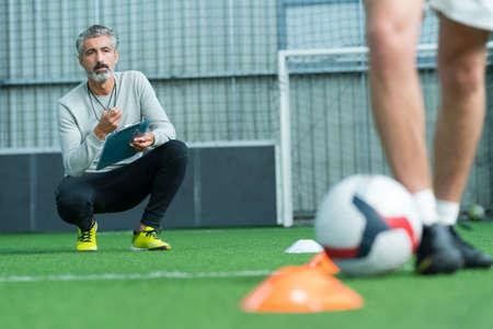 Photo pour football coach watching young man training - image libre de droit