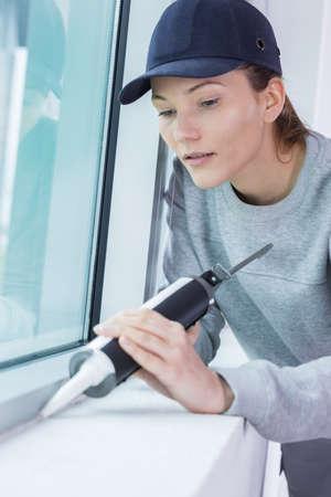 Photo pour female construction worker installing window in house - image libre de droit