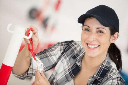 Photo pour female builder erecting a plastic chain around work site - image libre de droit