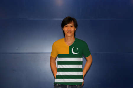 Foto de Man wearing Azad Kashmir flag on shirt and standing on the blue wall background. Green background with four white stripes; a gold canton and a star and crescent. - Imagen libre de derechos