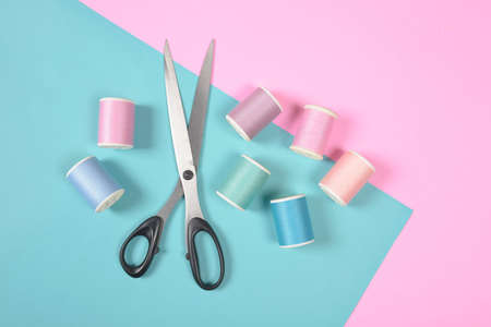 Foto de Flat lay of colored thread rolls and Scissors for sewing on two tone background, Sewing and needlework concept. - Imagen libre de derechos