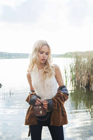 Foto für Beautiful blonde woman wearing flared jeans, a white lace top and a brown jacket, posing on the lake. Hippie, Boho Style. Baby's face model - Lizenzfreies Bild