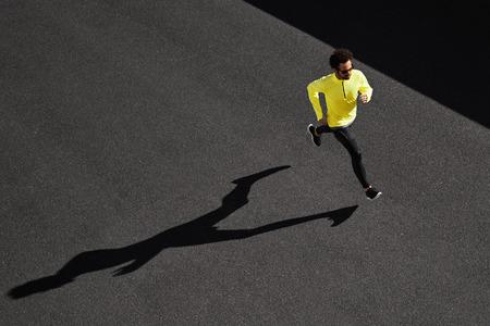 Foto de Running man sprinting for success on run. Top view athlete runner training at fast speed at black asphalt. Muscular fit sport model sprinter exercising sprint in yellow sportswear. Caucasian fitness model in his 20s. - Imagen libre de derechos