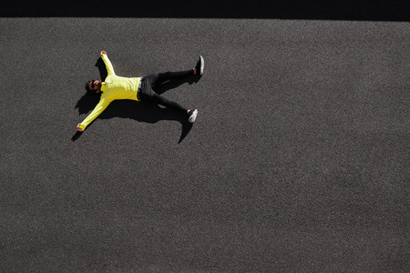 Photo pour Top view runner in yellow sportswear resting lying on a black asphalt after running. Jogging man taking a break during training outdoors. Caucasian fitness model 20s in Barcelona, Spain. - image libre de droit