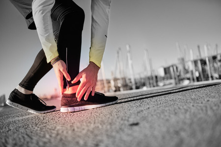 Foto de Broken twisted ankle - running sport injury. Athletic man runner touching foot in pain due to sprained ankle. - Imagen libre de derechos