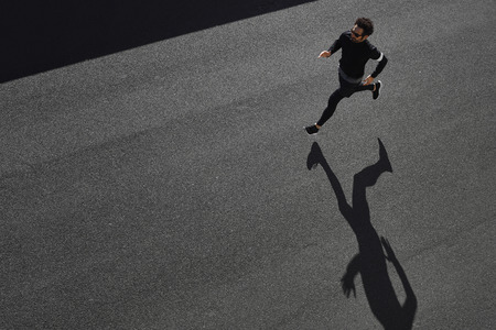 Foto de Top view athlete runner training at road in black sportswear at central position. Muscular fit sport model sprinter exercising sprint on city road. Full body length of Caucasian model. - Imagen libre de derechos