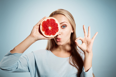 Photo for Young blonde woman with grapefruit in her hands studio portrait isolated on blue background. Young blond woman showing OK sign about the benefits of vitamin C - Royalty Free Image