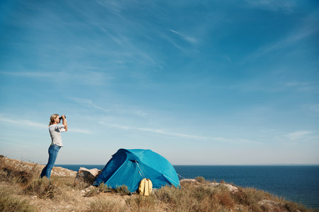 Foto de Young active female standing on the top of mountain and watching away in binocular, extreme lifestyle, traveling and trek concept - Imagen libre de derechos