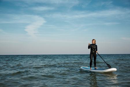 Photo pour Young blonde female paddles a paddleboard at the sea - image libre de droit