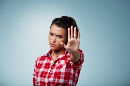 Photo for Angry woman gesturing stop sign over isolated backgound. Focus on hand - Royalty Free Image