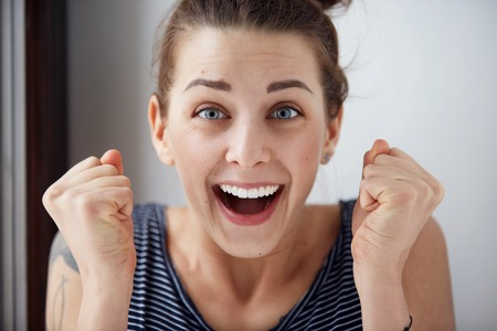 Foto de Surprised woman with hands up amazed or shocked by unexpected news holding close palms up and showing happy expression. Young adult woman on greybackground - Imagen libre de derechos