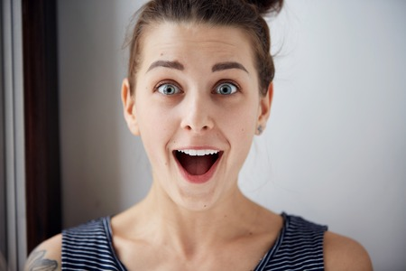 Photo pour Surprise astonished woman. Closeup portrait woman looking surprised in full disbelief  wide open mouth isolated grey wall background. Positive human emotion facial expression body language. Funny girl - image libre de droit
