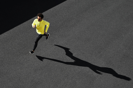 Foto de Running man sprinting for success on run. Top view athlete runner training at fast speed at asphalt. Muscular fit sport model sprinter exercising sprint in yellow sportswear. Caucasian fitness model - Imagen libre de derechos