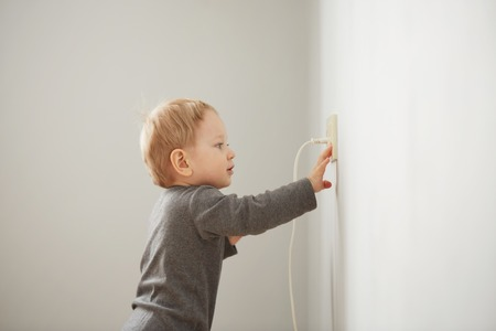 Photo pour Curious little boy playing with electric plug. - image libre de droit