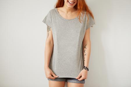 Foto de Girl wearing grey blank t-shirt standing on the background of a white wall. - Imagen libre de derechos