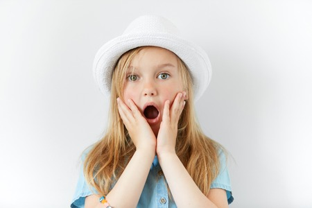 Photo for Headshot of pretty surprised little girl wearing white hat and denim shirt with hands on cheeks looking at the camera with astonished or shocked expression, mouth wide open. Human facial expressions - Royalty Free Image