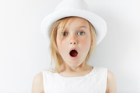 Photo for Portrait of emotional beautiful blonde little girl wearing trendy white clothes. Adorable surprised preschool child looking at the camera in astonishment with mouth wide open. shocked with something - Royalty Free Image