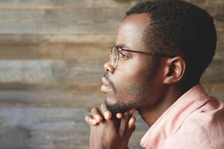 Foto de Profile headshot of young black man in glasses, with hairy, healthy face, looking into the distance, contemplating the beauty, with his chin on his crossed hands, isolated on a wooden background - Imagen libre de derechos