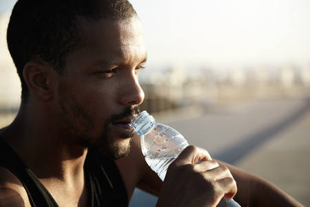Photo pour Healthy lifestyle concept. Profile portrait of black man with athletic body sitting on pavement in morning sun after training exercises in open air, holding bottle, drinking water, looking far away - image libre de droit