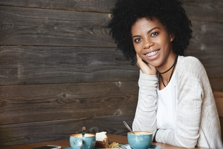 Photo for Human emotions and feelings. Young attractive and charismatic dark-skinned woman with curly hair, wearing casual clothes, drinking coffee with cake posing with big smile showing her teeth in braces - Royalty Free Image