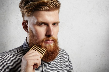 Photo pour Portrait of young attractive redhead hipster male with serious and confident look, holding wooden comb and doing his thick beard. Stylish bearded barber in checkered shirt combing in salon. Horizontal - image libre de droit