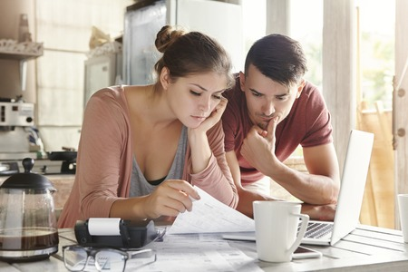 Foto de Worried young Caucasian married couple reading important notification from bank while managing domestic finances and calculating their expenses at kitchen table, using laptop computer and calculator - Imagen libre de derechos
