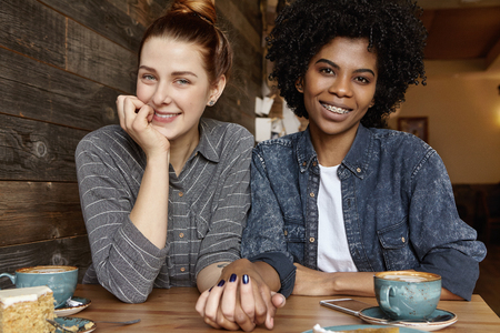 Photo pour Interracial gay couple relaxing indoors. Cute Caucasian woman with hair bun holding hand of her stylish African girlfriend during lunch. Two lesbians celebrating their anniversary at restaurant - image libre de droit