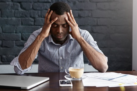 Photo pour Frustrated young African-American businessman having bad headache, squeezing his temples, feeling stressed at work, sitting at desk with generic laptop computer, documents, mug and mobile phone - image libre de droit