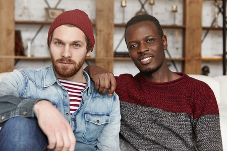Foto de Homosexual love and relationships concept. Interracial gay couple relaxing at cafe: African-American man in sweater holding hand on his stylish bearded Caucasian boyfriend's shoulder in trendy hat - Imagen libre de derechos