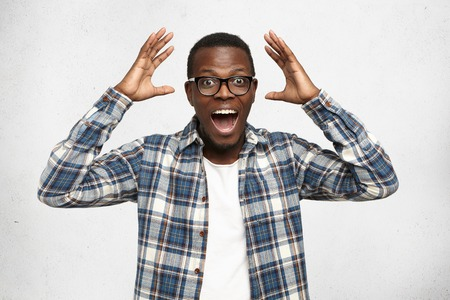 Photo pour I can't believe this. Amazed young African American hipster wearing trendy glasses and checkered shirt over white t-shirt holding hands in surprised gesture, keeping mouth wide open, looking shocked - image libre de droit
