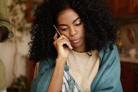 Photo pour Serious young dark-skinned female with Afro hairstyle having worried and unhappy look while talking on mobile phone, receiving bad negative news, sitting alone at kitchen table wearing wrap - image libre de droit