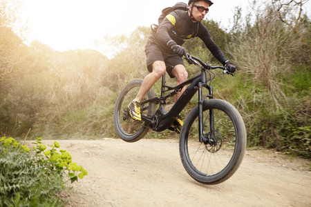 Photo pour Cyclist in action jumping high on black electric motor-powered bicycle down trail in woods. Young rider wearing glasses and helmet making extreme biking stunt on e-bike while exercising outdoors - image libre de droit