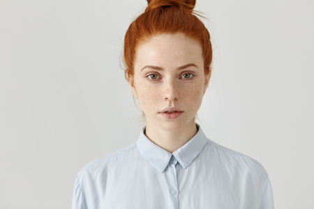Photo for Close up shot of attractive successful young red-haired businesswoman in formal shirt having serious confident look before working day, posing at white office wall. People and lifestyle concept - Royalty Free Image