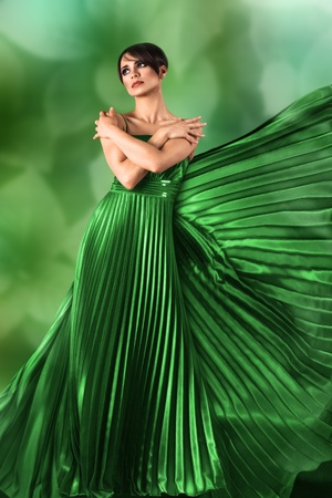 Sexy young girl in long flowing dress against green nature background