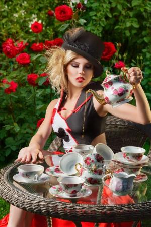 Foto de Young woman posing as magnificent card queen from wonderland at mystic tea-party - Imagen libre de derechos